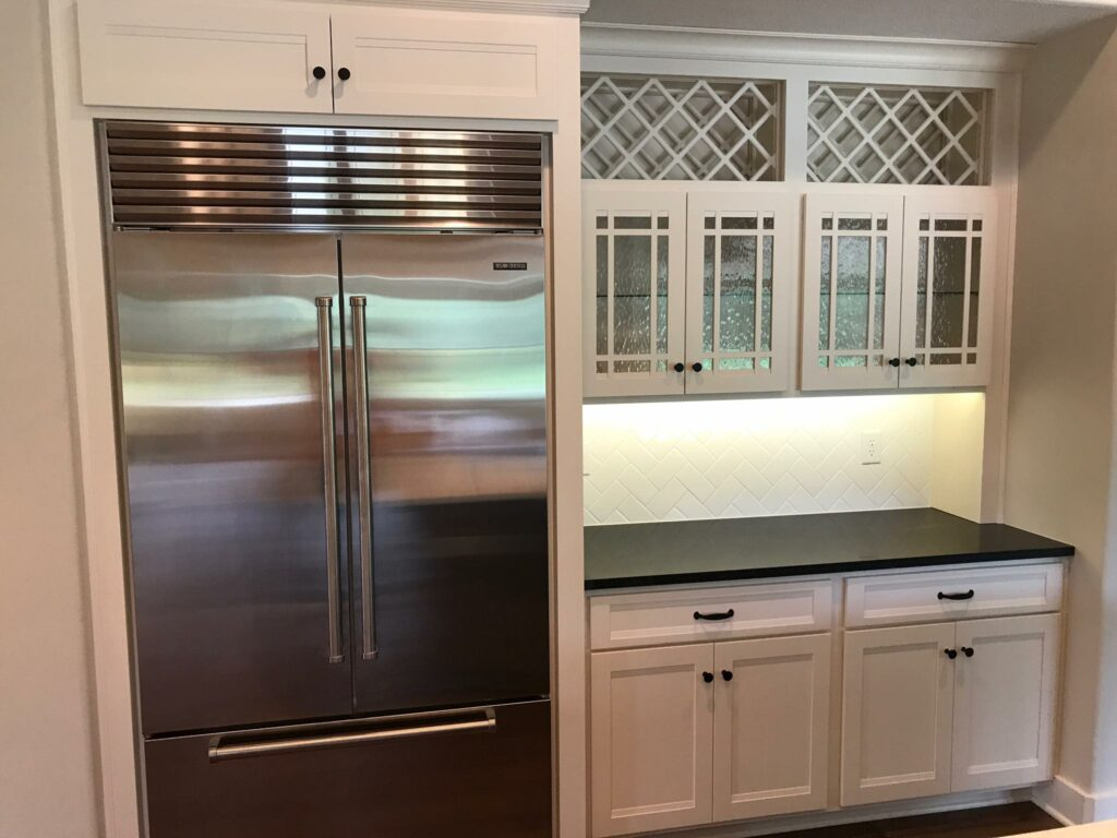 kitchen with white cabinets and stainless steel refrigerator