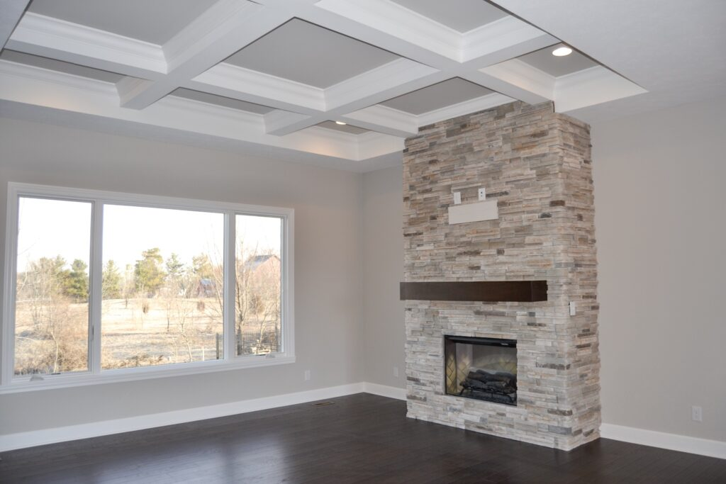 living room with stone fireplace in center