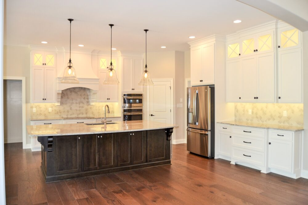 Kitchen with white cabinets and dark brown accents