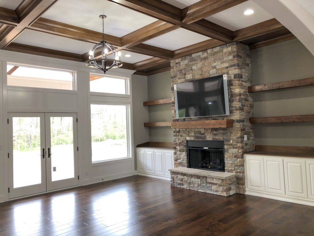 living room with brick fireplace with brown built in shelves