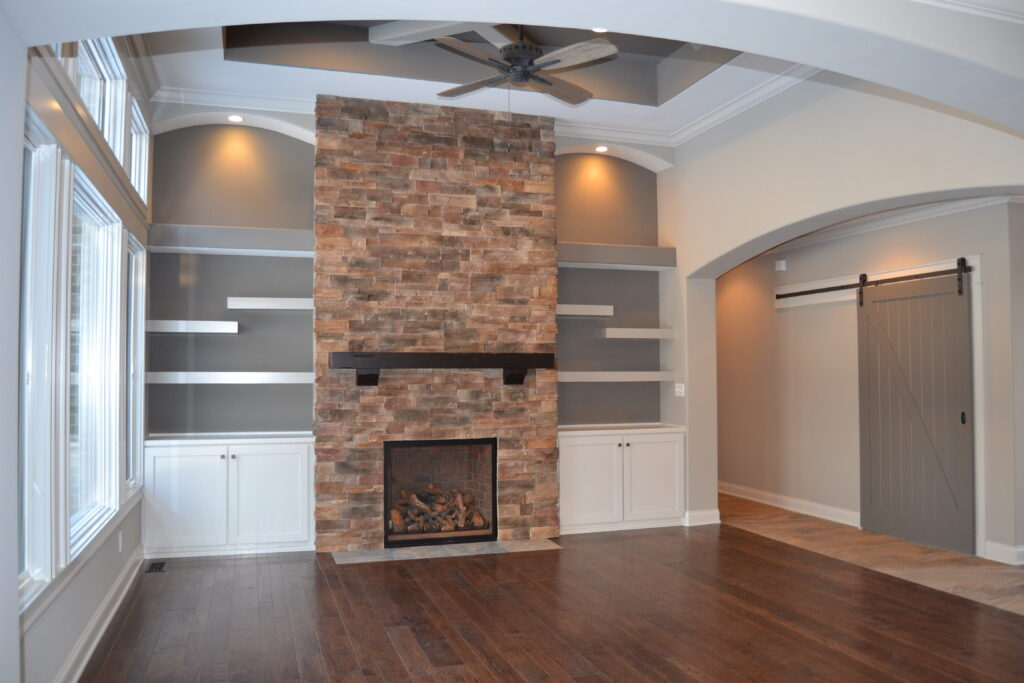 living room with brick fireplace with white built in shelves