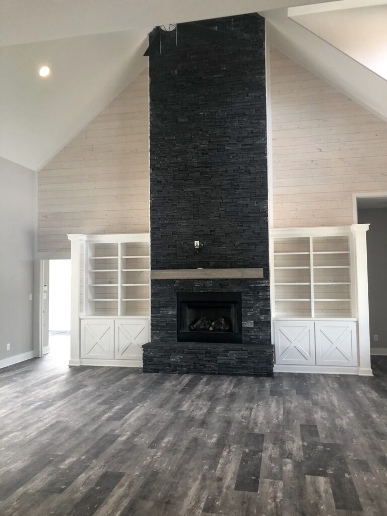 living room with black stone fireplace with white built in shelves