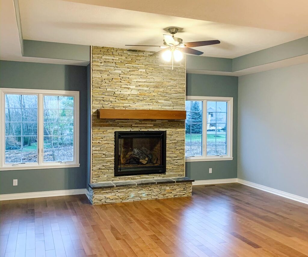 living room with brick fireplace with green walls