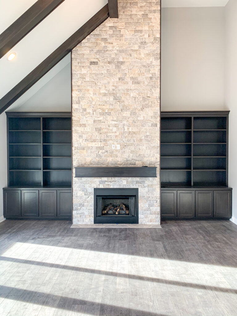 living room with brick fireplace and dark brown built in shelves