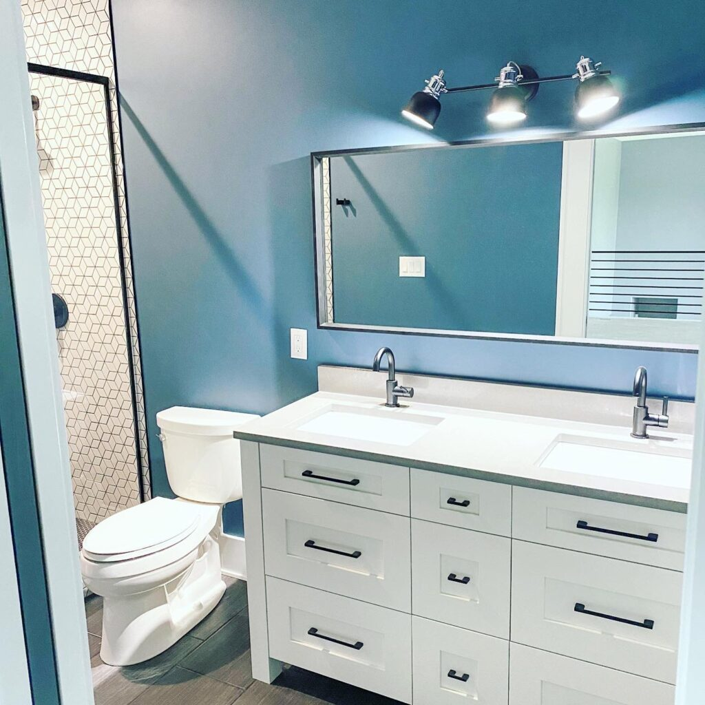 bathroom with white cabinets and countertops. blue walls