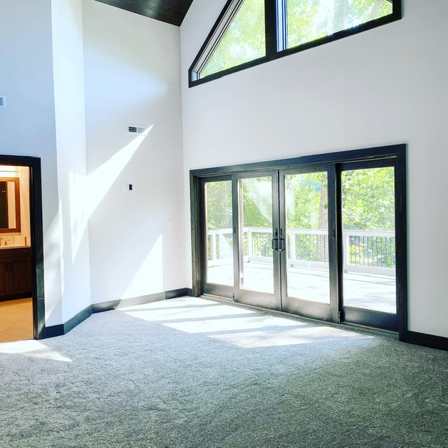 Living room with sliding glass door, white walls, and dark wood trim