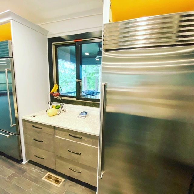 Two industrial refrigerators with cabinets and countertop in between