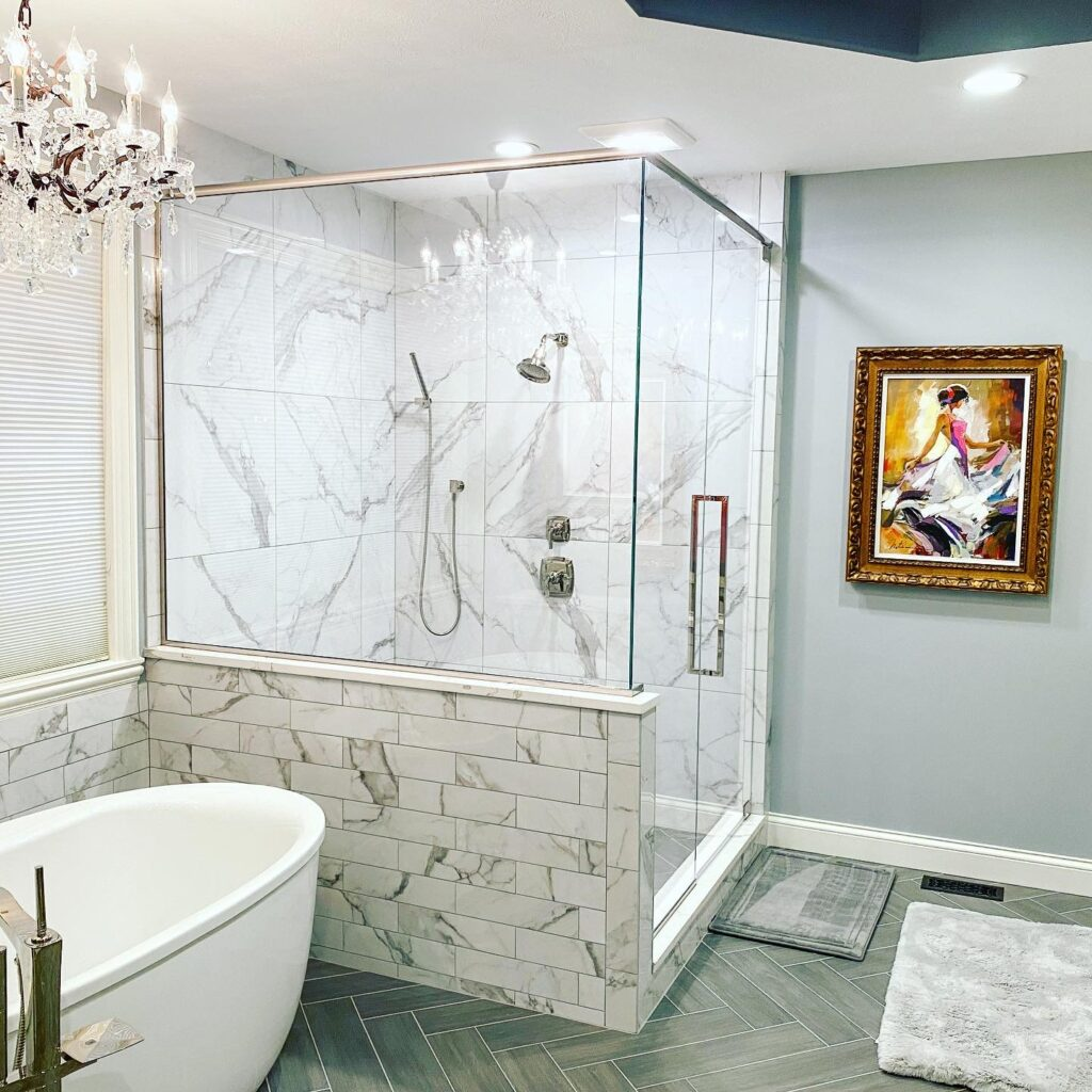 Bathroom with white tub, chandlier, and glass shower